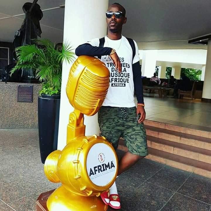 Eddy Kenzo standing next to the Afrima Statue Award